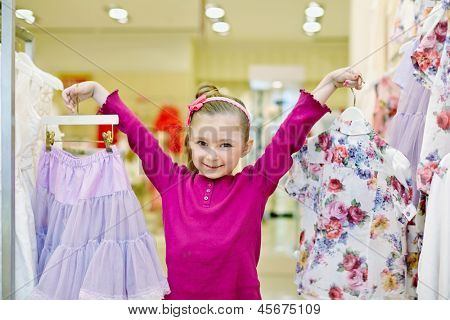 Joyfully smiling little girl shows hangers with light-violet skirt and flower-patterned blouse