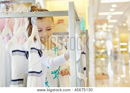 Little girl looks with interest upon dresses hanging on rack in clothing store