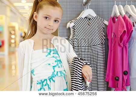 Little girl stands holding striped gown over her arm in clothing store