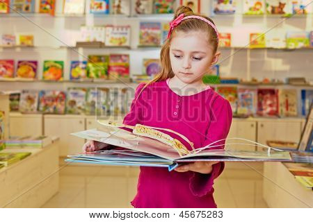 Little girl views fold-out book on anatomy in book department at store