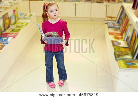 Little girl stands holding open book in book department at store