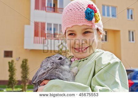Smiling little girl in greenish jacket and knitted hat stands holding rabbit in her hands