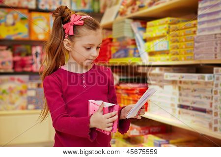 Little girl views pack of envelopes in book department of store