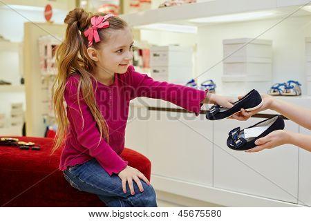 Niña sentada en el imperio otomano, lleva zapatos de manos del vendedor