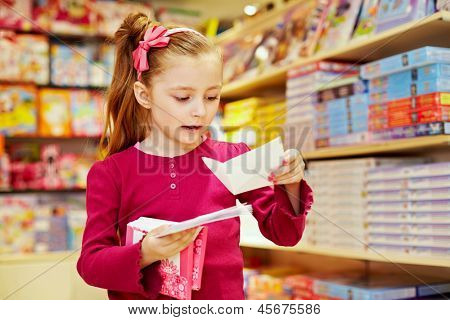 Little girl holds pack of envelopes in one hand and one open envelope in another