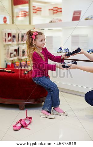 Little girl sits on ottoman in new shoes and takes another one pair from female hands