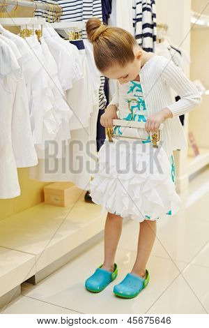 Little girl tries on short white skirt in clothing store