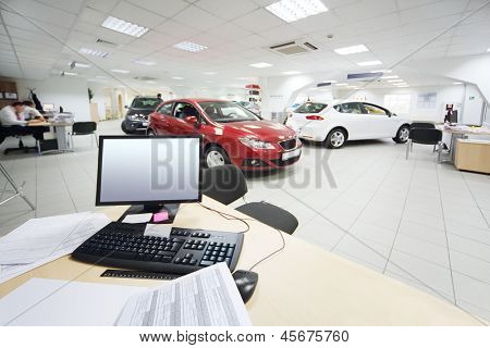 Computer and documents on wooden table and new cars stand in office of car shop.