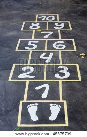 Hopscotch painted indelible ink on black asphalt for children outdoor.