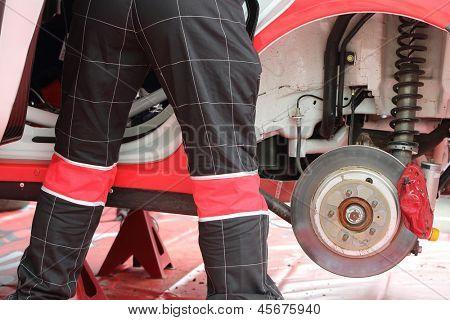 Automobile mechanic do diagnostics of car before start the race.