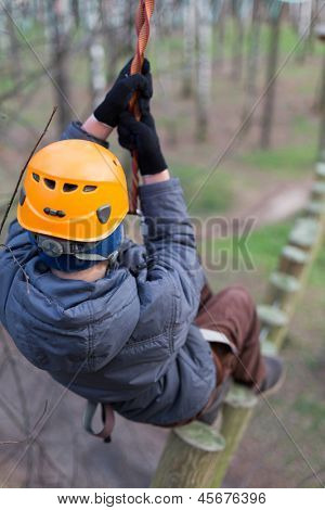 Little climber walks on logs holding safety rope