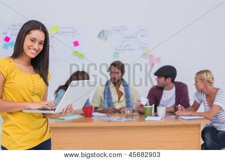 Prettty editor using laptop as team works behind her at large desk in office