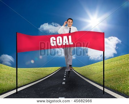 Businessman running on a road with a banner with goal written on it