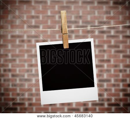 Instant photo hung with peg with bricks on the background