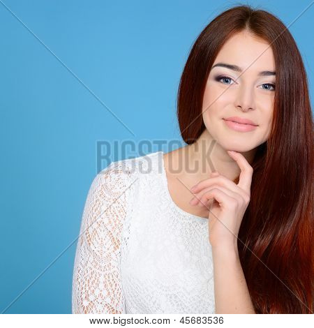 Young attractive woman's portrait, beautiful girl with long hair and white dress, over blue studio shot