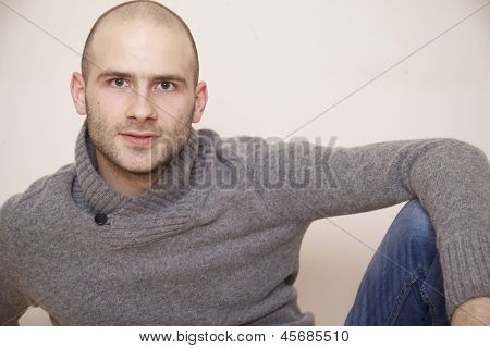 fashion portrait of handsome young man in a gray sweater isolated on white background