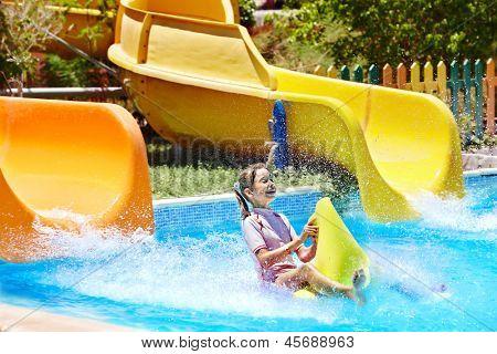 Child on water slide at aquapark. Summer holiday..
