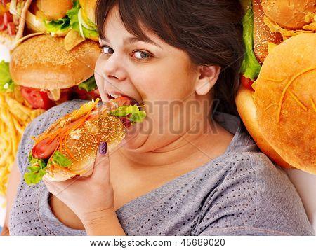 Overweight woman holding hamburger.