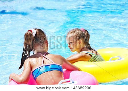 Children sitting on inflatable ring in swimming pool.Rear view.