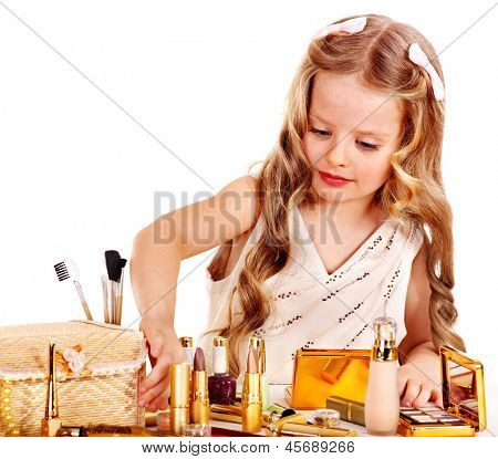 Child cosmetics. Little girl applying make up.