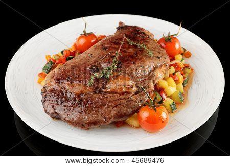 Ribeye saboroso bife com legumes stir fritado isoladas no fundo preto