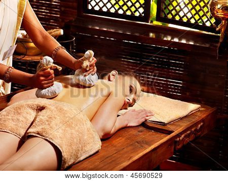 Woman having Ayurveda massage with herbal ball.