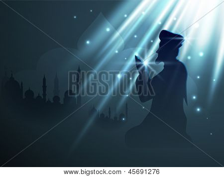 Silhouette of Muslim person in traditional dress reading Namaj (Islamic Prayer) on blue background with text Ramadan Kareem.