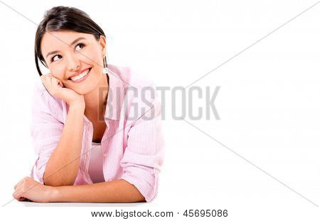 Thoughtful woman lying on the floor smiling - isolated over white