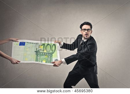 young businessman pulling money