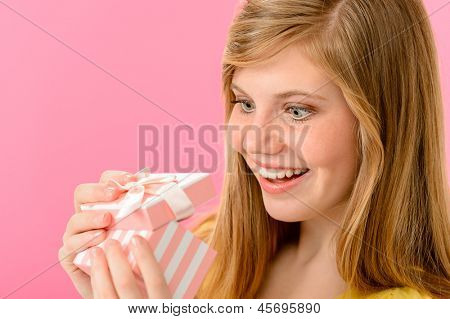 Elated girl opening gift isolated on pink background