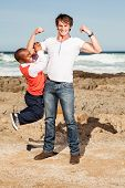 pic of midget  - dwarfish african man hanging playfully on a young caucasian mans arm on the rocky beach - JPG