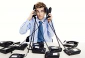 image of telemarketing  - Young man in the office and answering several phones at the same time - JPG