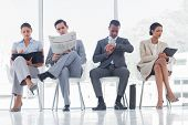 stock photo of crossed legs  - Waiting room with business people sat in line - JPG