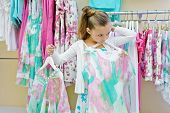 Little girl tries on dress in clothing store