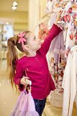 stock photo of take off clothes  - Little girl takes off hangers with dresses from stand in clothing store - JPG