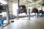 Four black cars on lifts in small service station. Cars prepared to diagnosis and repair.