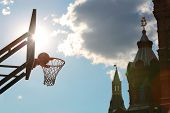 A silhouette of a basketball ball in the basket against the sky, the clouds and the Kremlin.