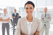 stock photo of arms race  - Attractive businesswoman with arms crossed standing in front of colleagues - JPG
