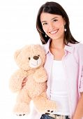 Casual woman holding a teddy bear and smiling - isolated over white