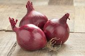 Whole red onions on the table