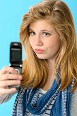Young girl taking picture of herself with mobile phone
