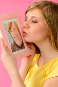 Young girl holding and kissing a picture of her love