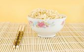 stock photo of lo mein  - delicious bowl of chinese lo mein noodles on a bamboo place mat with chopsticks - JPG