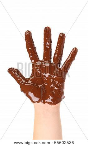 Children's hand stained with chocolate frosting.