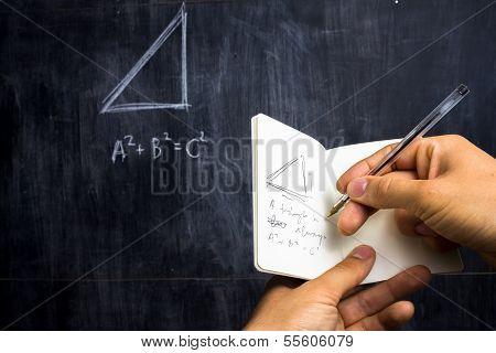 Man Taking Notes Of Math Theorem On Blackboard