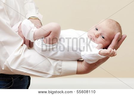 newborn baby girl lying on arm