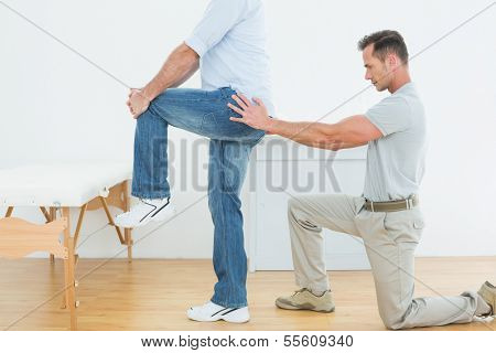 Side view of a male physiotherapist examining man's back in the medical office
