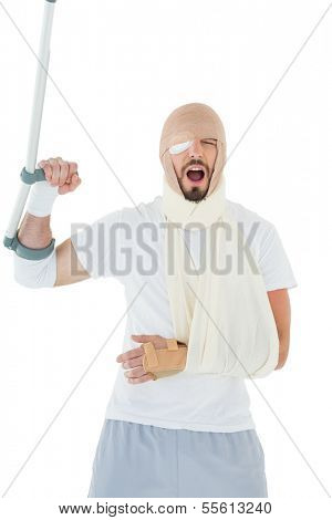 Cheerful young man with broken hand and crutch cheering over  white background