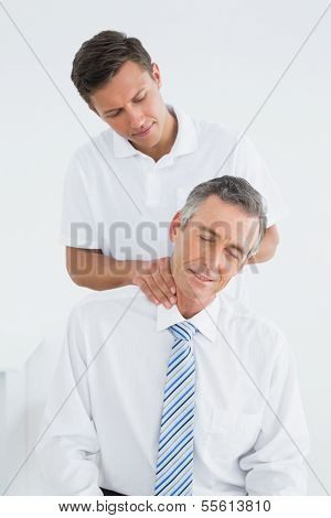 Male chiropractor massaging patients neck over white background