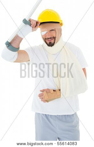 Portrait of a young man in hard hat with broken hand and crutch over  white background
